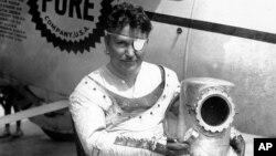 와일리 포스트가 지난 1934년 뉴욕의 비행장에 세워둔 '위니메이'호 앞에서 사진을 찍고 있다.