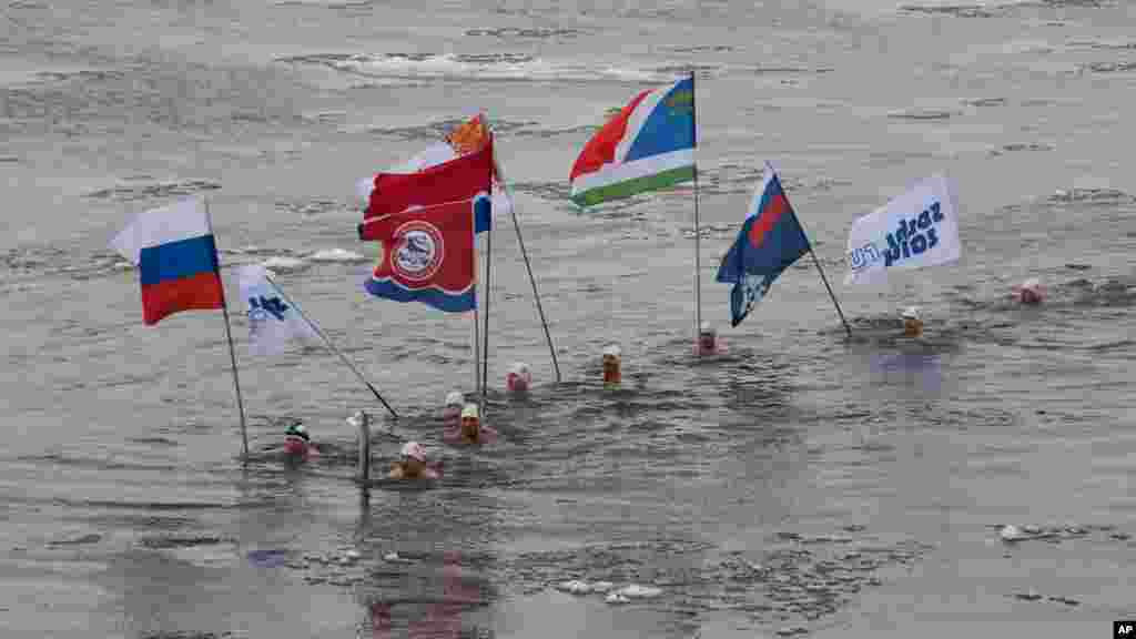 Pembawa obor Olimpiade musim dingin Socchi 2014, Alexander Brylin, bersama para perenang lainnya membawa obor olimpiade melintasi sungai Amur di kota Blagoveshchensk, Rusia timur.