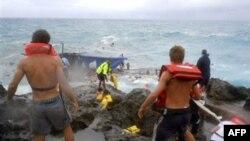 Nhân viên cứu hộ trên bờ đá ở đảo Christmas nỗ lực cứu các nạn nhân trên chiếc thuyền gỗ bị vỡ, ngày 15/12/2010