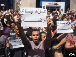 "Egyptian protesters hold a sign that says ""Awad sold his land"" in Arabic during protest against the transfer of power of two Red Sea islands from Egypt to Saudi Arabia in downtown Cairo, April 15, 2016. The Egyptian proverb refers to shame some locals fee"