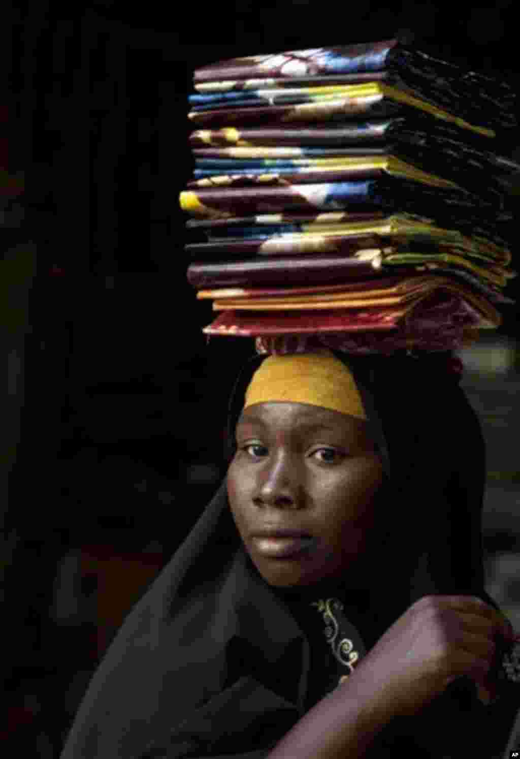 A cloth seller waits in hope of selling some pieces to a wholesale buyer, as sellers said their business was suffering following the recent coup, at the Grand Market in Bamako, Mali Saturday, March 31, 2012. The countries neighboring Mali have condemned t