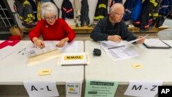 Poll clerk Kay McClain, left, and Duane Fleener, prepare the voter lists as they get ready for the doors to open at 6 a.m. Nov. 4, 2014, at their poll location in a fire station in Avon, Ind.