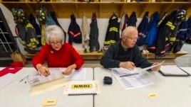 Nhân viên bầu cử chuẩn bị danh sách cử tri trước khi phòng phiếu mở cửa tại Avon, Indiana.