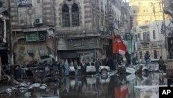 Warga berkumpul di sekitar lokasi pasca ledakan di sebuah markas polisi di kawasan Delta Nil, kota Mansoura, Mesir (24/12).