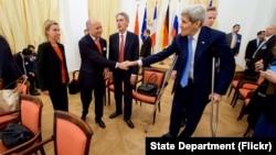 美国国务卿克里在参加伊朗核会谈前和法国外长法比尤斯握手(2015年7月10日)