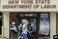 Pejalan kaki melewati kantor Departemen Tenaga Kerja di New York, 11 Juni 2020.