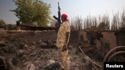 남수단 보르에서 한 군인이 정부군과 반군의 교전으로 불타버린 농가에 서있다. (자료사진)