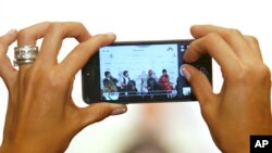 A journalist takes a photo using a smart phone during a press conference, file photo.