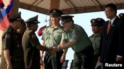 Bộ trưởng Quốc phòng Campuchia Tea Banh (trái) bắt tay với cố vấn quân đội Trung Quốc trong một buổi lễ tốt nghiệp tại Học viện quân đội ở tỉnh Kampong Speu, Campuchia.