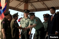 FILE - Cambodian Defense Minister Tea Banh, second left, shakes hands with a Chinese army adviser during a graduation ceremony at the Army Institute in Kampong Speu province. Cambodia has backed Chinese maritime claims across islands and waters in the South China Sea.