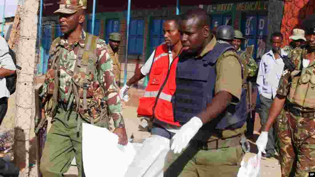 Des agents de la police kenyane portent un cadavre à Mandera, au Kenya, après une attaque des djihadistes Al-Shabaab, qui a couté la vie à 14 personnes, 7 juillet 2015.