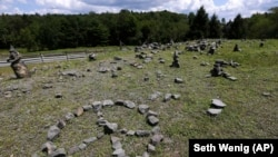 In this Wednesday, July 24, 2019, photo, a flat piece of ground and rock cairns are all that remain of the stage of the 1969 Woodstock Music and Arts Fair in Bethel, New York.