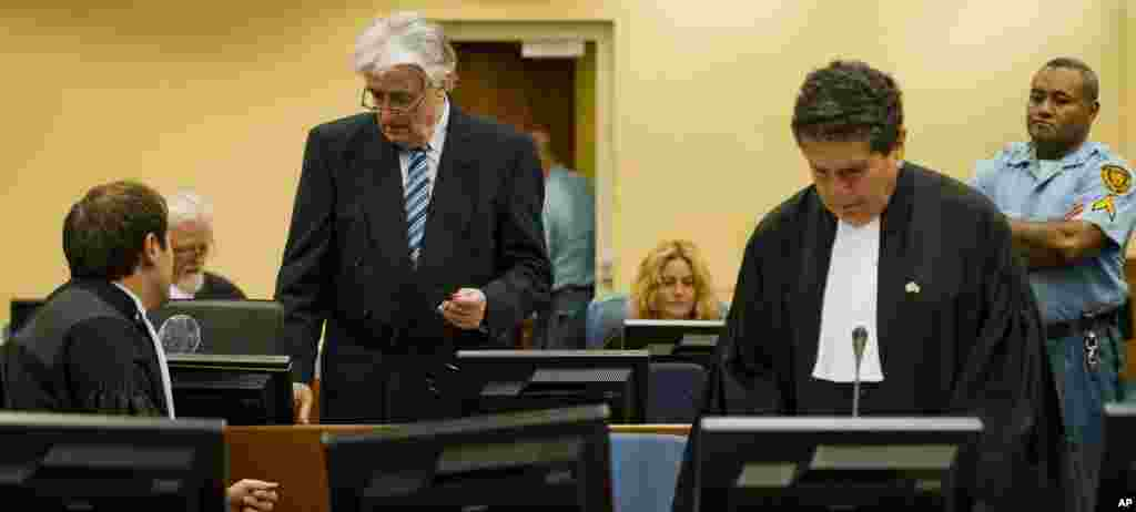 Radovan Karadzic, standing at left, talks to Marko Sladojevic, left, a member of his legal team while his legal advisor Peter Robinson, right, prepares ahead of the start of Karadzic's defense.