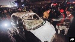 پولیس اور ریسکیو اہلکار لاھور میں بم دھماکے کے بعد ایک کار کا معائنہ کر رہے ہیں۔ 25 جنوری، 2011