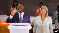 Presiden Pantai Gading Alassane Ouattara (kiri) setelah memberikan suaranya di sebuah TPS bersama istrinya Dominique Ouattara, di Abidjan (25/10). (AP/Schalk van Zuydam)