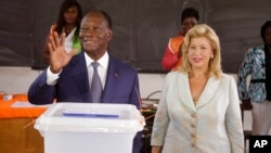 FILE - Ivory Coast's president Alassane Ouattara, left, waves after casting his ballot with his wife, Dominique Ouattara, right, at a polling station during elections in Abidjan, Ivory Coast, Sunday Oct. 25, 2015.
