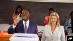 ປະທານາທິບໍດີ Ivory Coast ທ່ານ Alassane Ouattara (ຊ້າຍ) ໂບກມືຫລັງຈາກປ່ອນບັດ ພ້ອມດ້ວຍພັນລະຍາ ທ່ານນາງ Dominique Ouattara (ຂວາ)