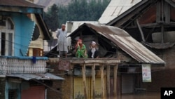 Flood-affected Kashmiris shout out for help from the roof of a house in Srinagar, India, Sept. 9, 2014.