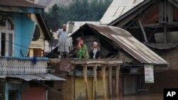 인도 카슈미르 지역 주민이 홍수로 물에 잠긴 집의 지붕에 올라가 도움을 요청하고 있다.