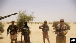 Fighters from Islamist group Ansar Dine stand guard during a hostage handover, in the desert outside Timbuktu, Mali. (file)