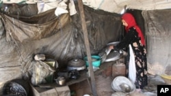 A refugee woman originally from the western Iraqi desert region, packs away pots and pans in her tent home several kilometers from the southern holy city of Karbala, some 110 kms from Baghdad (2009 file photo)