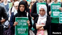 FILE - A woman holds a poster during a rally in support of asylum seekers in central Sydney.