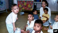 A group of Cambodian orphans gather and play while an orphanage worker looks on (File photo).
