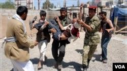 Seorang tentara Yaman yang membelot, membantu mengangkat seorang demonstran anti pemerintah yang terluka dalam bentrokan di Sana'a (18/10).