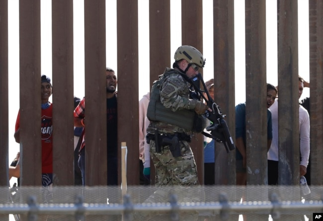 FILE - A U.S. Customs and Border Protection officer walks along a wall at the border between Mexico and the United States, as seen from San Diego, California, Nov. 25, 2018.