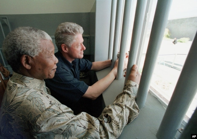 FILE - In this March 27, 1998 file photo, Nelson Mandela and former US president Bill Clinton look to the outside from Mandela's Robben Island prison cell in Cape Town, South Africa.