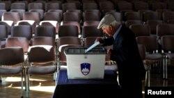 Čovjek ubacuje svoj glasački listić u kutiju, Vodice, Slovenija, 3. juni 2018.