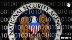FILE - A tablet computer shows the logo of the United States' National Security Agency (NSA) against the backdrop of code in this multiple-exposure demonstration photo.