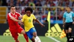 El brasileño Willian, a la derecha, es desafiado por el serbio Filip Kostic durante el partido del grupo E entre Serbia y Brasil, en la Copa Mundial de fútbol 2018 en el Estadio Spartak en Moscú, Rusia, miércoles 27 de junio de 2018. (AP Photo / Rebecca Blackwell)