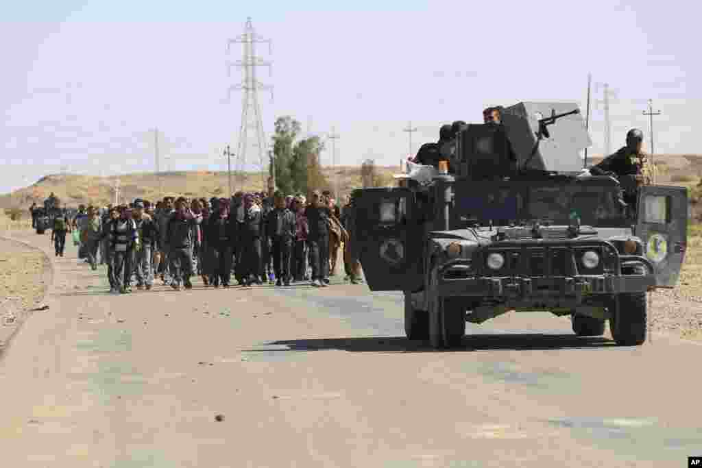 Counterterrorism forces escort people fleeing their homes during clashes between Iraqi security forces and the Islamic State group in Hit, 85 miles (140 kilometers) west of Baghdad, Iraq.
