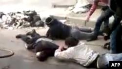 Những người đàn ông thu hồi một thi hài trên một con đường ở Homs, Syria hôm 15/12/11