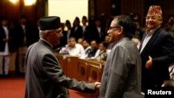 尼泊尔总理奥利(左)在议会宣布辞职后与尼泊尔共产党主席普拉昌达握手