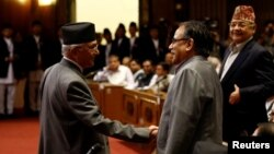 Nepal's Prime Minister Khadga Prasad Sharma Oli, also known as KP Oli, shakes hand with Chairman of the Unified Communist Party of Nepal (Maoist) Pushpa Kamal Dahal, also known as Prachanda, (R) as he returns after announcing his resignation at the parlia