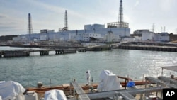A US military barge carrying pure water (bottom) leaves the quay near Tokyo Electric Power Co.'s Fukushima Daiichi Nuclear Power Plant on April 4, 2011.