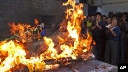 Tibetan exiles pray next to the burning funeral pyre of 27-year-old Jamphel Yeshi, who died two days after he immolated himself in Dharmsala, India, March 30, 2012.