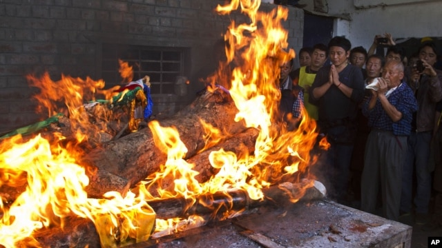 Tibetan exiles pray next to the burning funeral pyre of 27-year-old Jamphel Yeshi, who passed away Wednesday morning two days after he immolated himself in New Delhi, in Dharmsala, India, March 30, 2012.