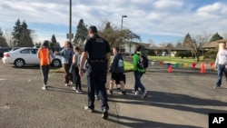 Eugene police officers and teachers escort students at Cascade Middle School to be reunited with their waiting parents outside St. Mark's Catholic Church in Eugene, Oregon., Friday, Jan. 11, 2019.