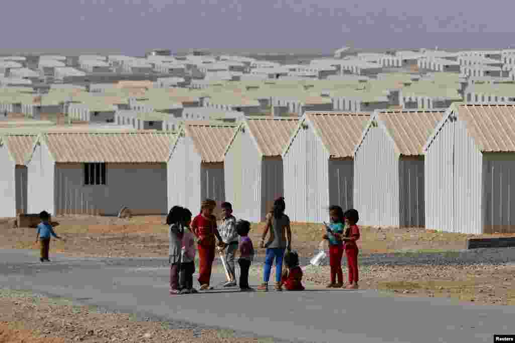 Syrian refugee children play in front of their family residences at Azraq refugee camp near Al Azraq, east of Amman, Jordan, Aug., 2014.