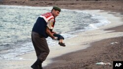 A paramilitary police officer carries the lifeless body of a migrant boy near the Turkish resort of Bodrum early Wednesday, Sept. 2, 2015. (AP Photo/DHA)