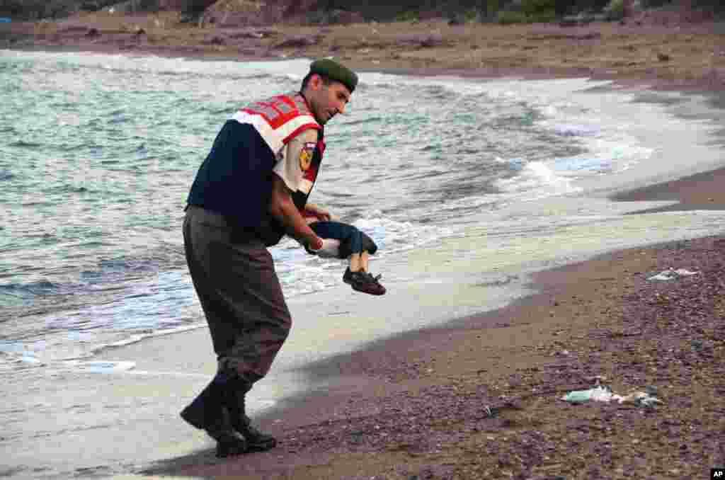 Suriyalik uch yashar kurd bola Alan Kurdining sohilda yotgan jasadi olib ketilmoqda, 2-sentabr, Bodrum, Turkiya