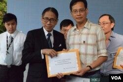 香港大學校委會主席梁智鴻(左)接收港大校友關注組召集人葉建源遞交的情願信。(美國之音湯惠芸攝)