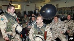 A balloon floats past Bulgarian soldiers with the NATO-led International Security Assistance Force (ISAF) as they celebrate New Year's eve at the US Camp Phoenix base in Kabul, Afghanistan, Dec 31, 2010 (File Photo)