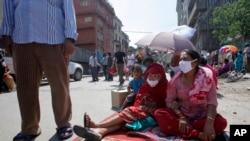 Mujeres nepalesas se colocan en el centro de una calle durante el terremoto de este martes en Bhaktapur, Nepal.