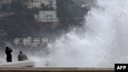 People watch giant waves, on Dec. 25, 2013 in Nice, southeastern France.