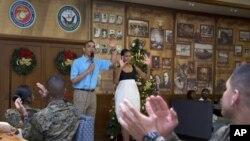 Presiden Amerika Barack Obama dan ibu negara Michelle Obama disambut meriah oleh para anggota dan keluarga militer AS di Anderson Hall, Pangkalan Angkatan Laut di Kaneohe, Hawaii , 25 Desember 2012. (AP Photo/Carolyn Kaster). Presiden Obama akan mempersingkat liburannya dan diperkirakan akan tiba kembali di Washington, Kamis pagi (27/12).