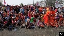 A Cambodian Buddhist monk, right, talks on a loud speaker as garment workers sit behind barbed wire set up by police near the Council of Ministers building during a rally in Phnom Penh, Cambodia, Monday, Dec. 30, 2013. The workers are demanding a raise in their monthly salary from US $160 to $80. (AP Photo/Heng Sinith)
